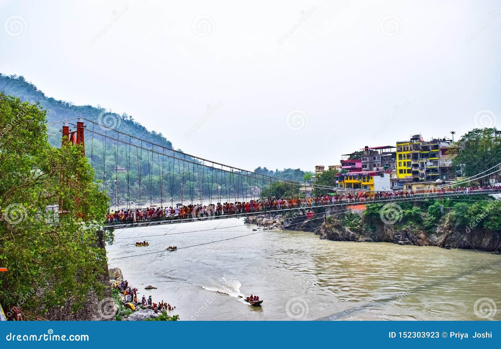 Ponte de suspensão do jhula de Lakshman em Rishikesh com os barcos no rio do ganga haridwar e em transportar