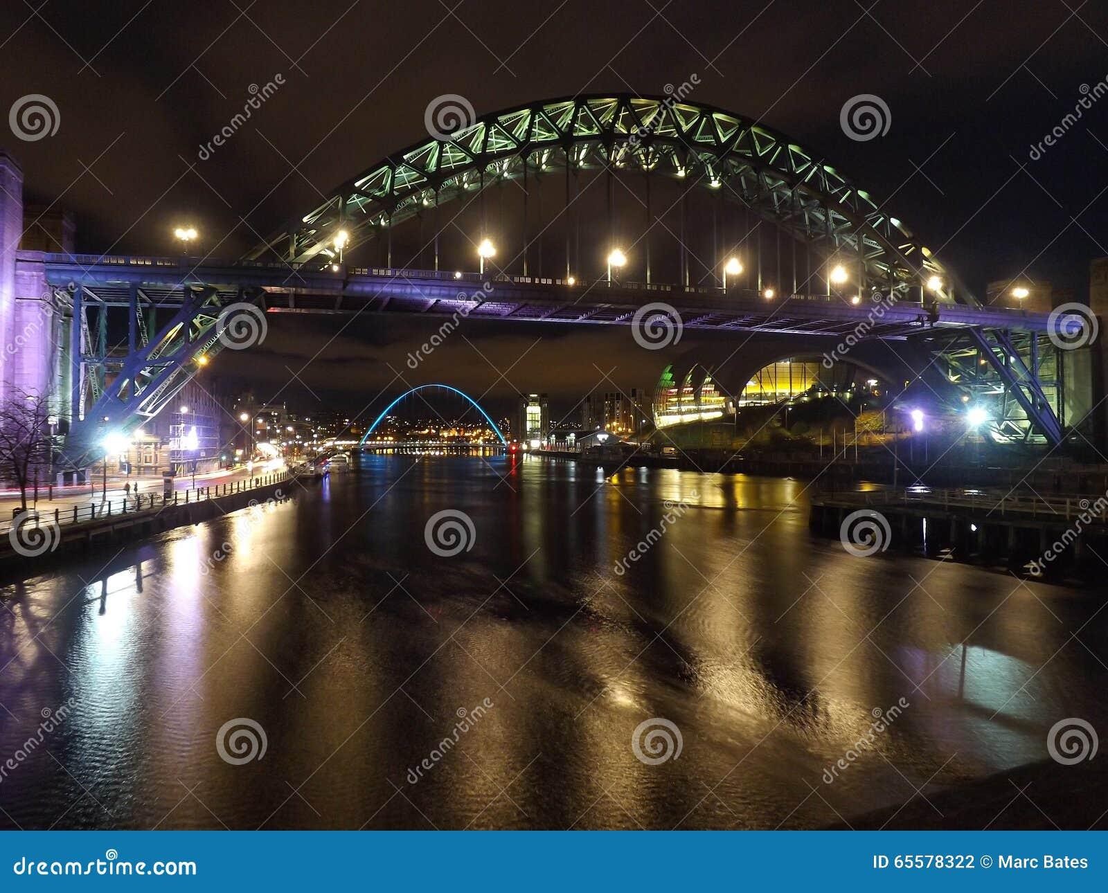 Ponte de Tyne na noite com a ponte do milênio no fundo