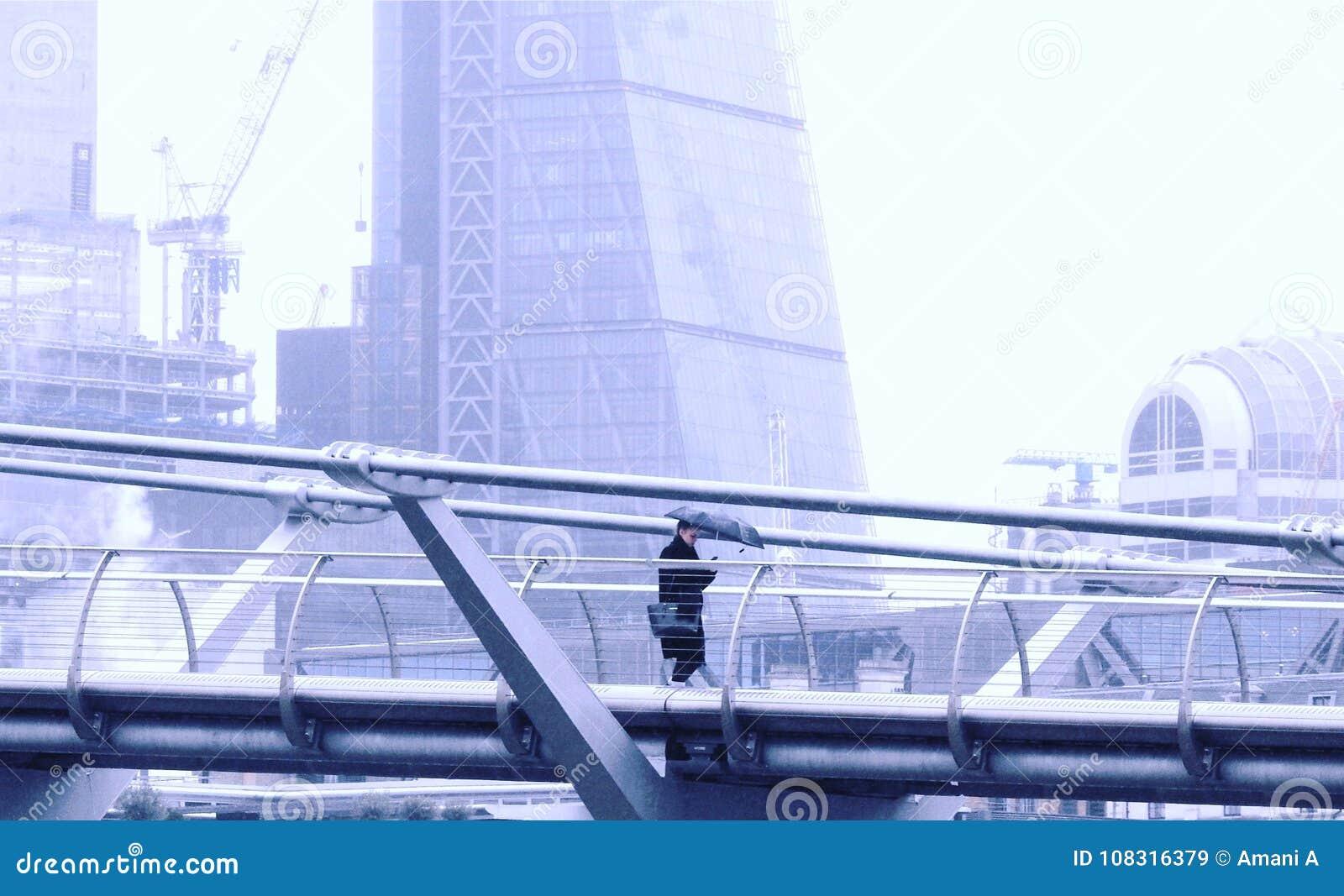Ponte do milênio, Londres Reino Unido 20 de janeiro de 2018 Uma senhora com o guarda-chuva que texting como anda apenas ao longo