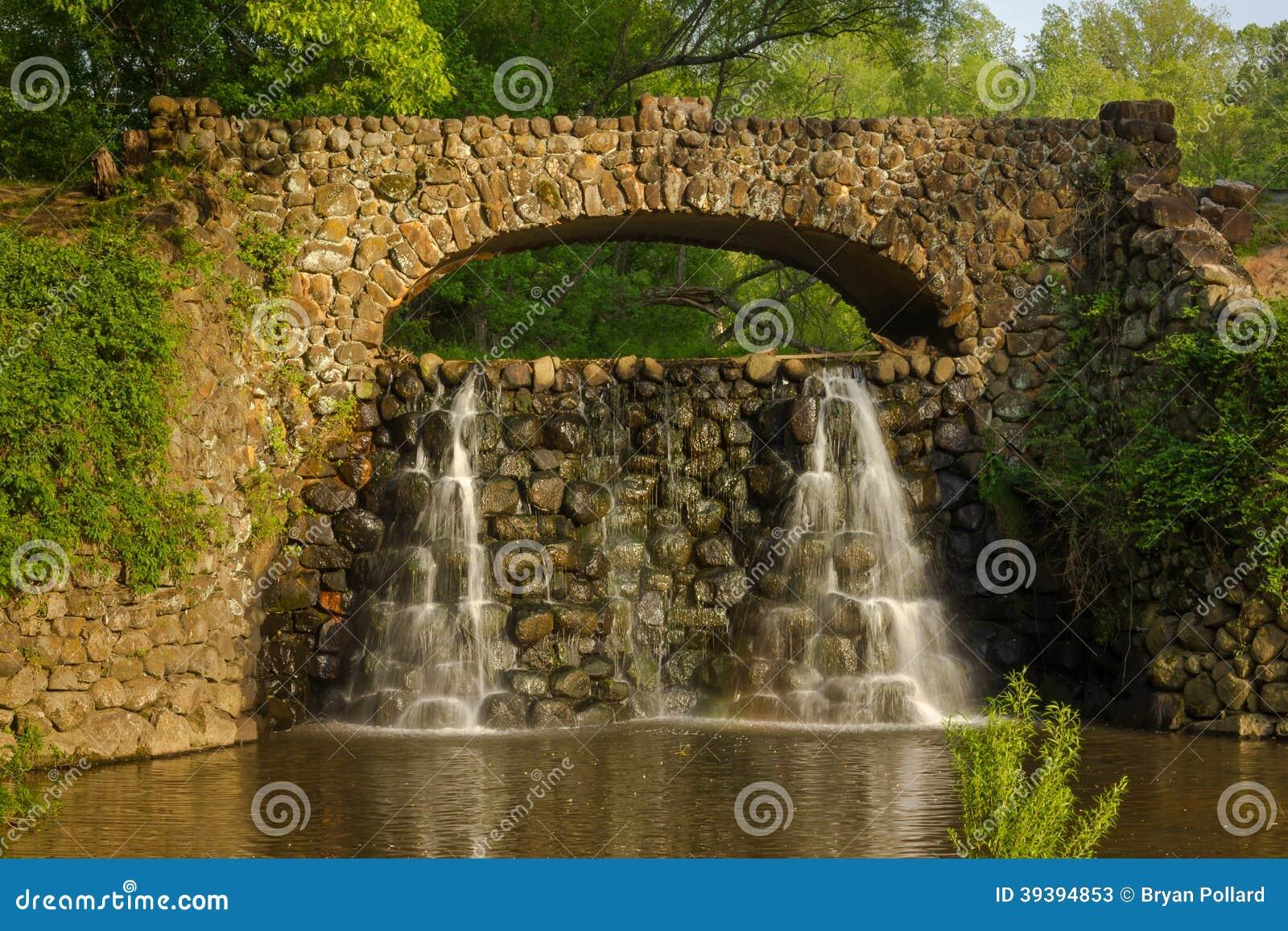Ponte e cascata di pietra nei giardini di reynolda immagine stock