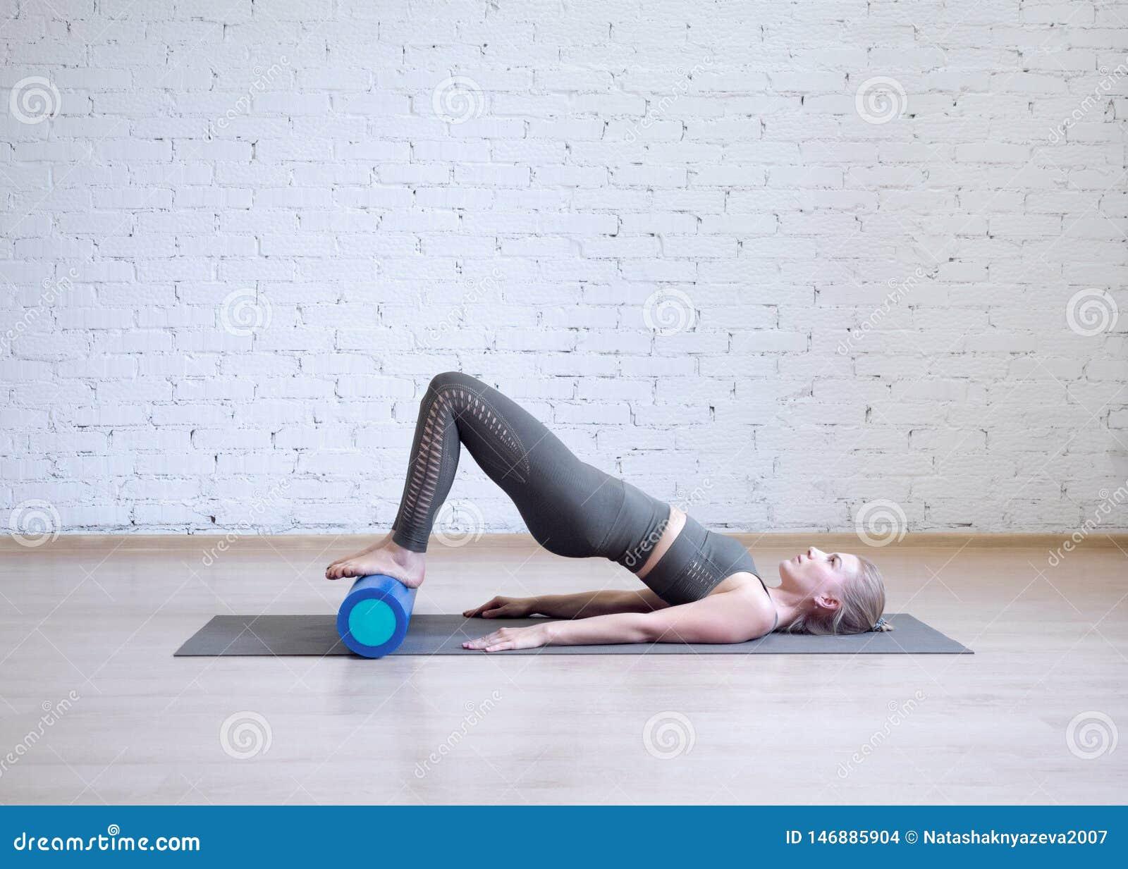Ponte Gluteal sul rullo della schiuma Giovane donna caucasica che fa i pilates con attrezzatura speciale nello studio di forma fi