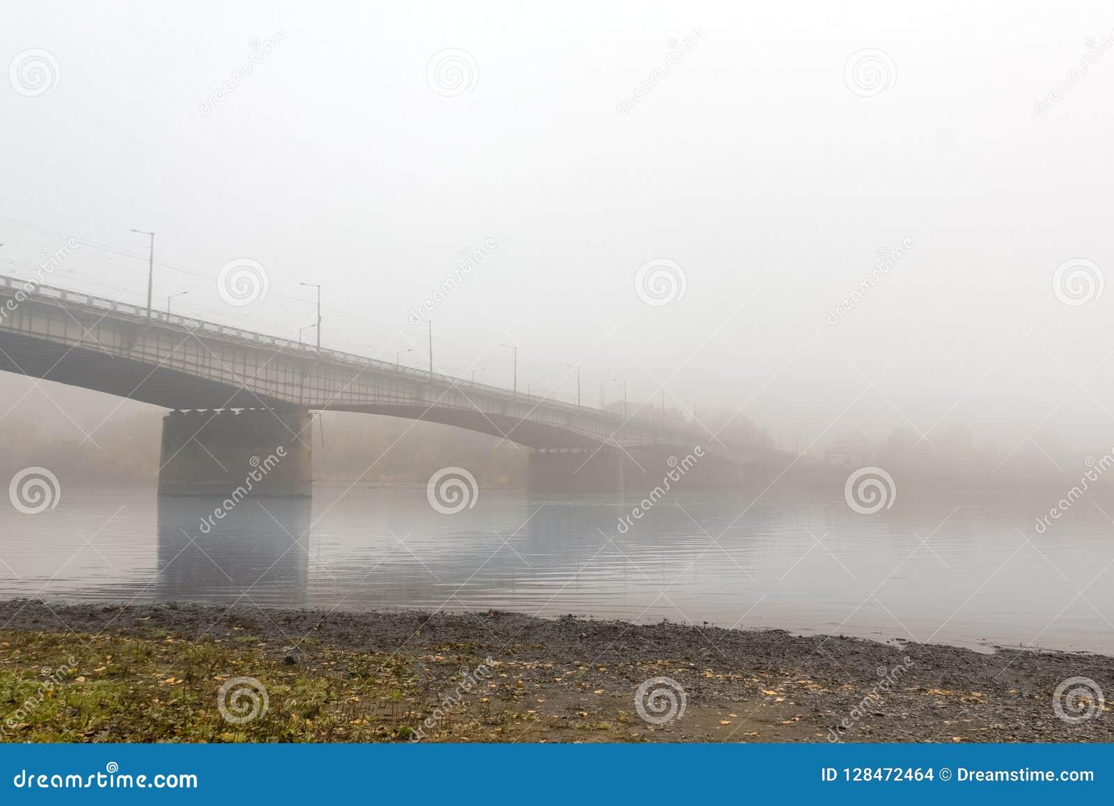 A ponte grande do automóvel esticou através de um rio calmo, envolvido dentro