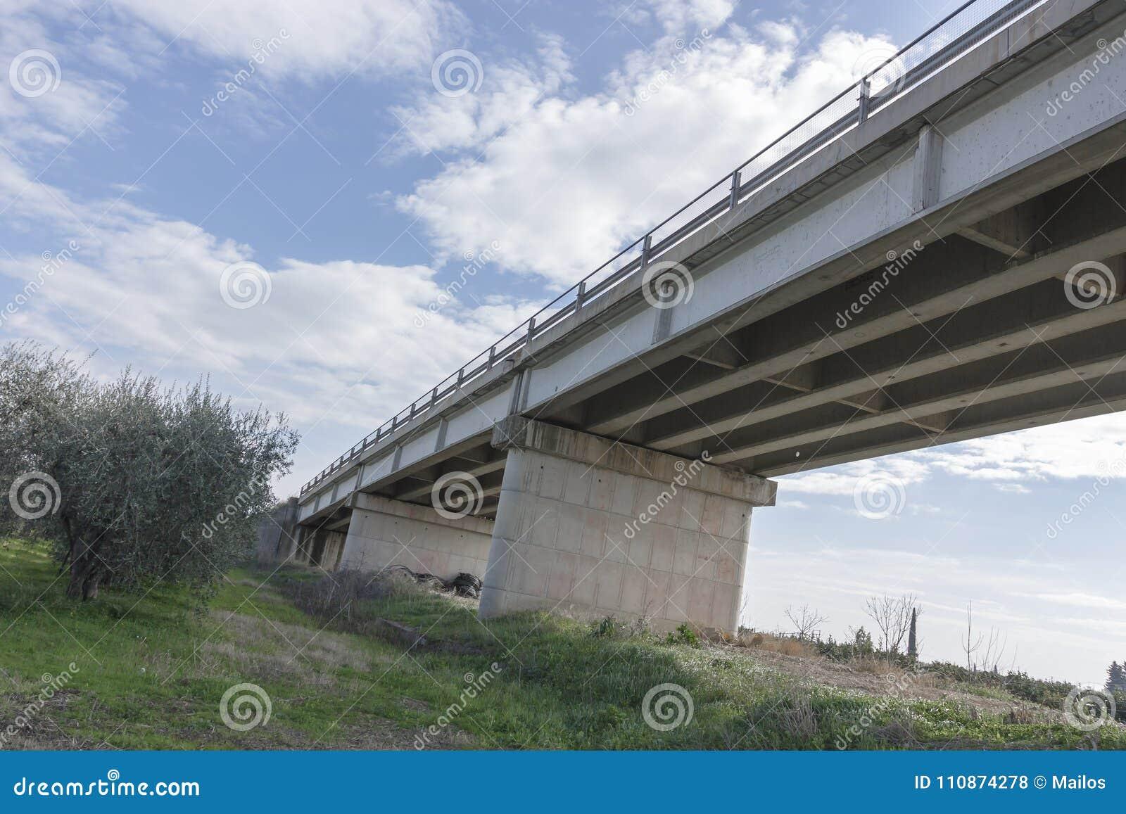Ponte que negligencia um campo da oliveira e na A.A. do fundo