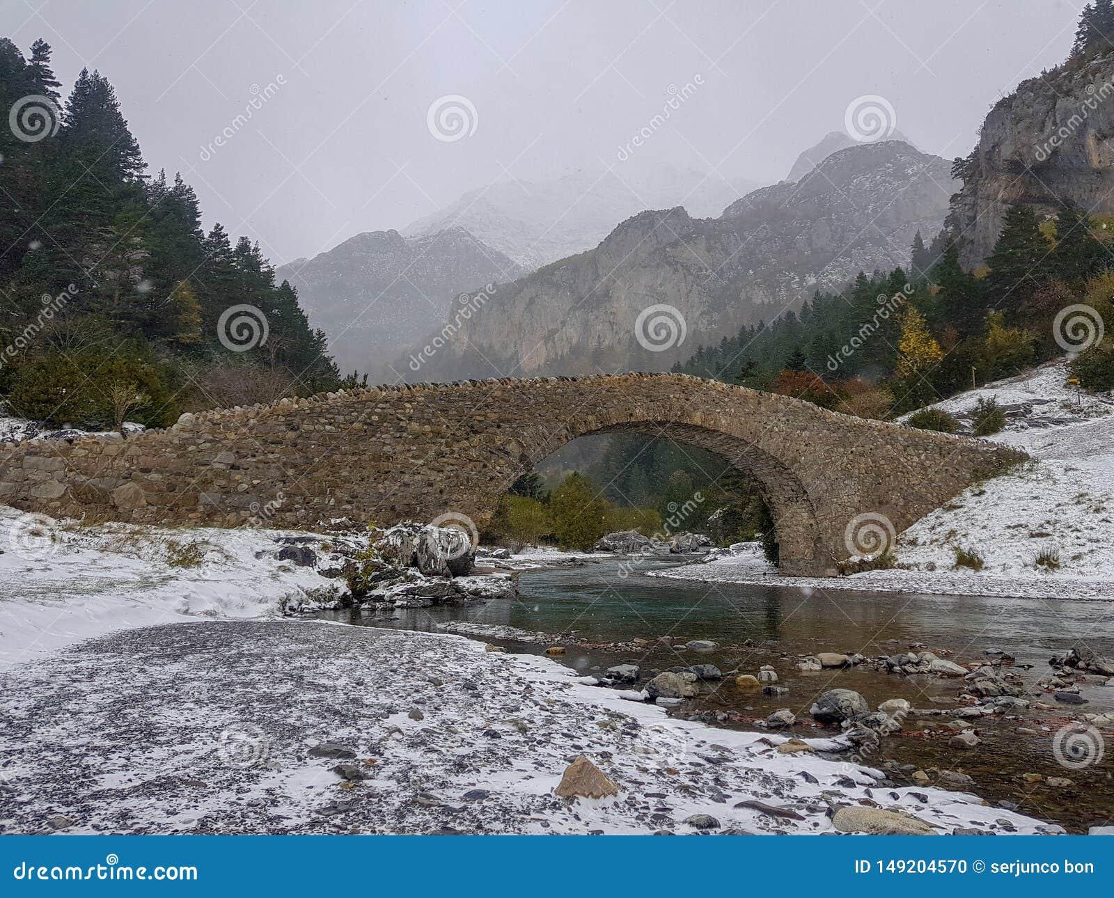 Ponte romana sobre o rio de Bujaruelo no parque nacional de Ordesa em Huesca, Espanha Imagem do dia nebuloso com as primeiras que