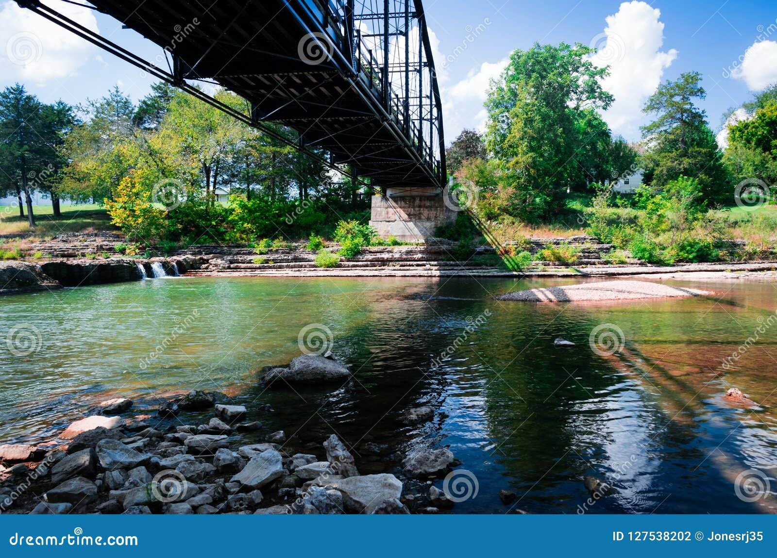 A ponte velha molda sombras coloridas nas rochas no rio abaixo