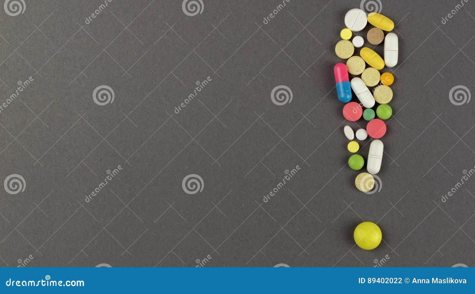 Ponto de exclamação criado dos comprimidos coloridos Conceito MÉDICO