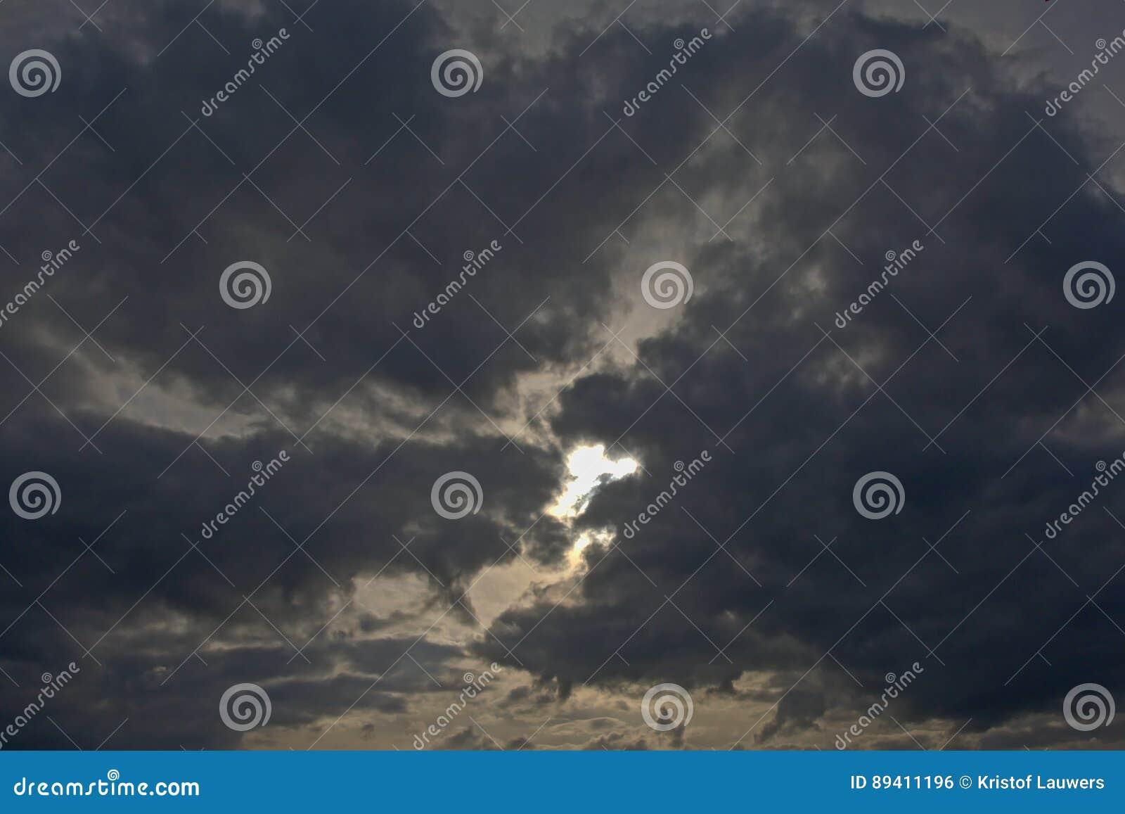Ponto de Sun que olha através das nuvens de tempestade escuras