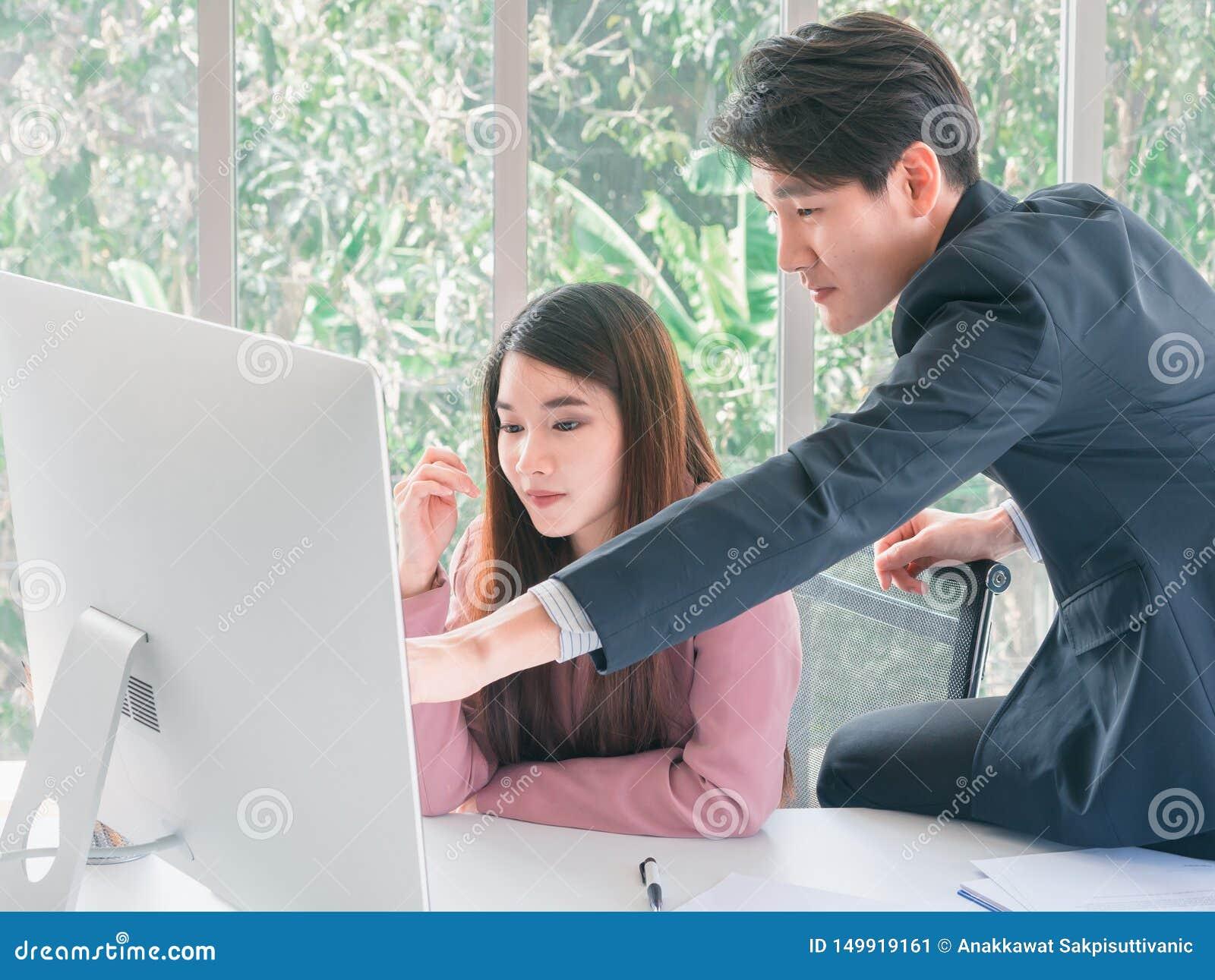 Ponto novo considerável asiático do homem de negócios para selecionar o monitor