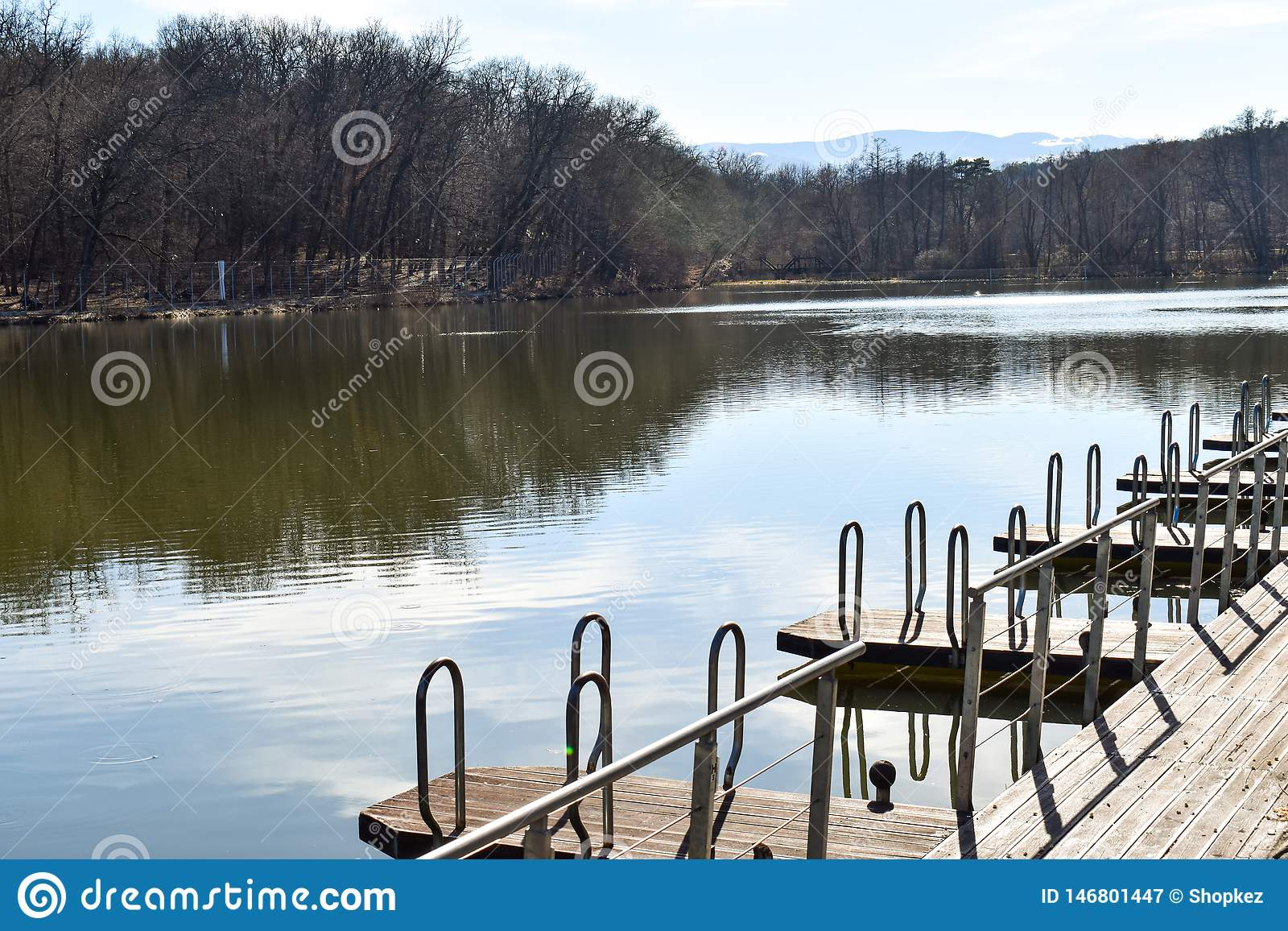 Pontoon wooden jetty pier for boat mooring marina on the park lake
