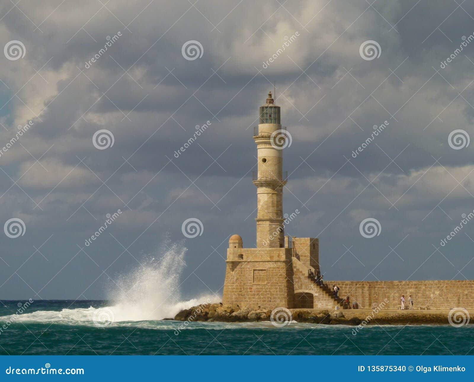 Ponure szare chmury wieszają nad latarnią morską żółte i białe cegły w Chania, o którym rozbijają fale