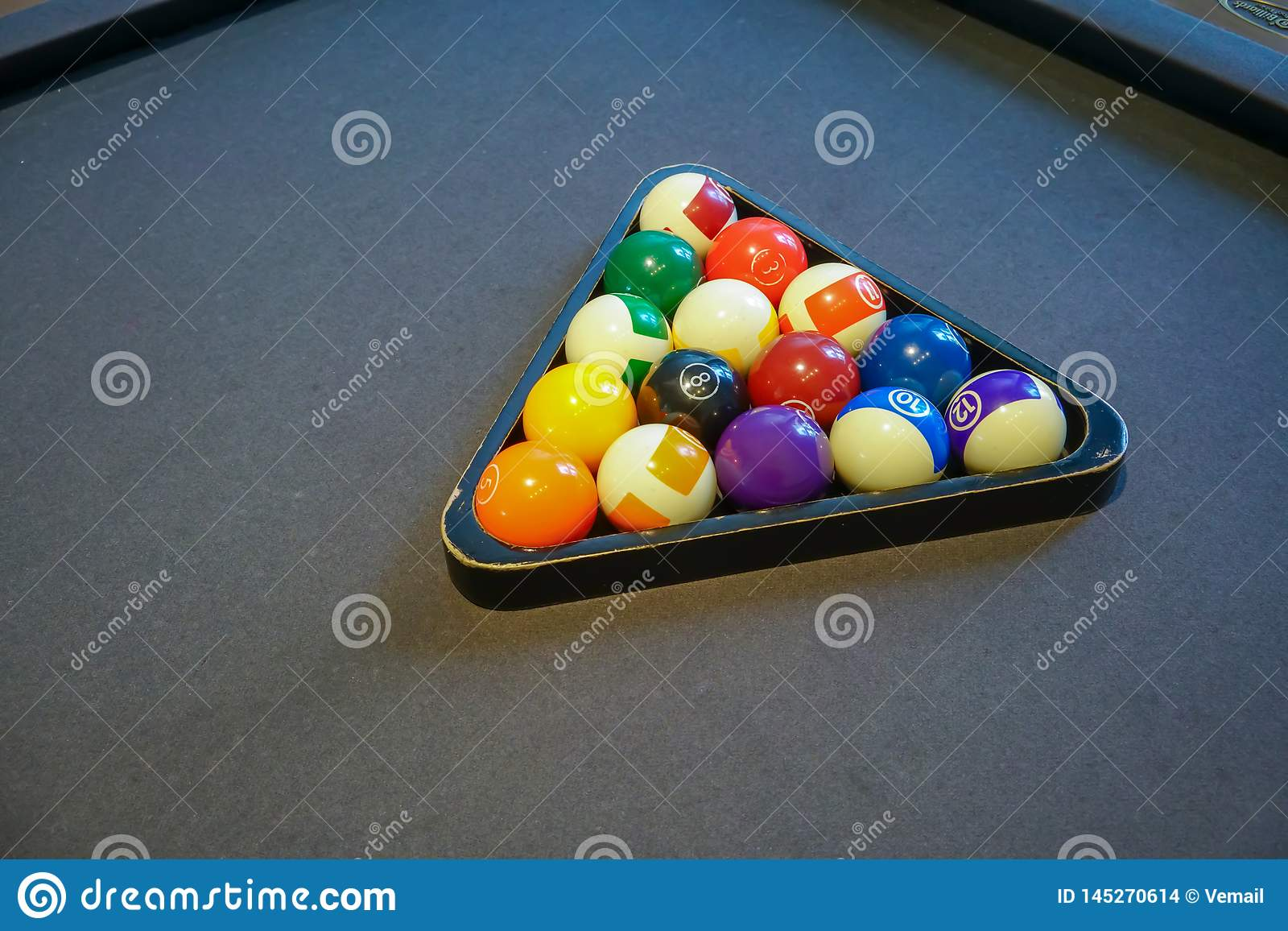 Pool billiard balls in a wooden rack on black background