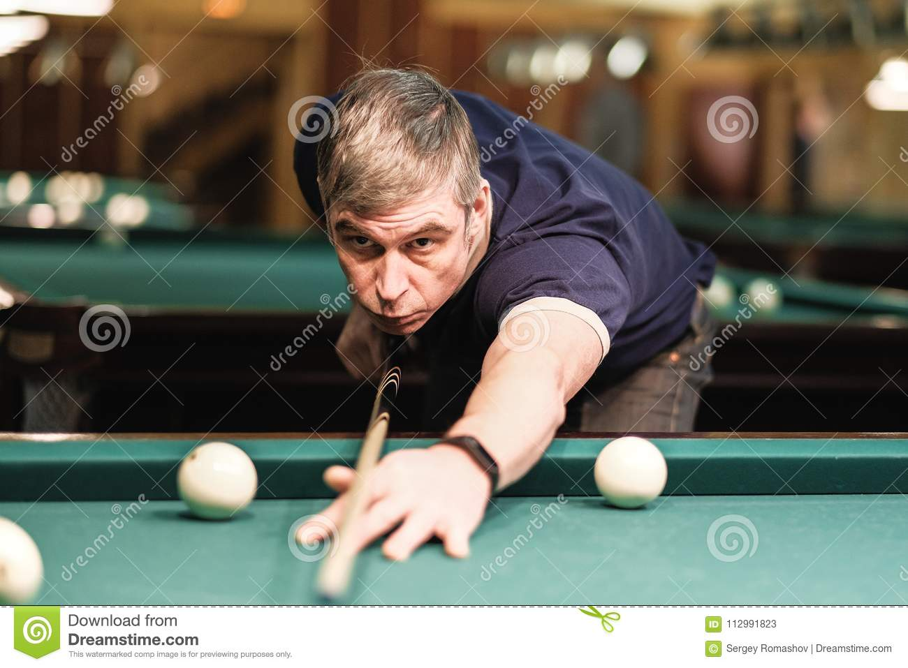A pool player takes aim at the ball