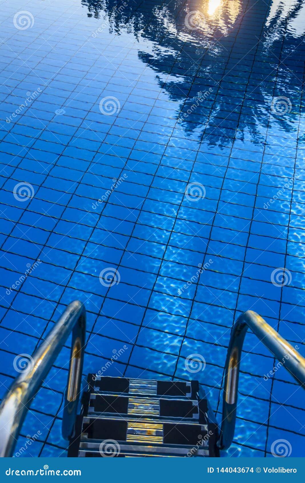 Pool trappasimning Sol på vatten för blå himmel: reflexion av solnedgången mellan palmträd på yttersidan av pölen