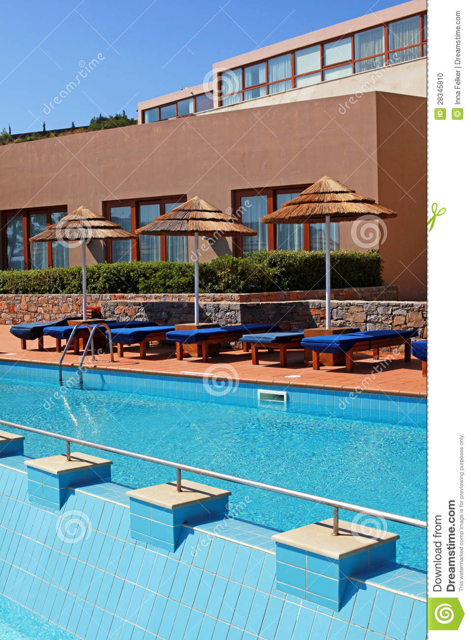 Poolside with pool bed and umbrella in luxury resort stock for Outdoor pool bed