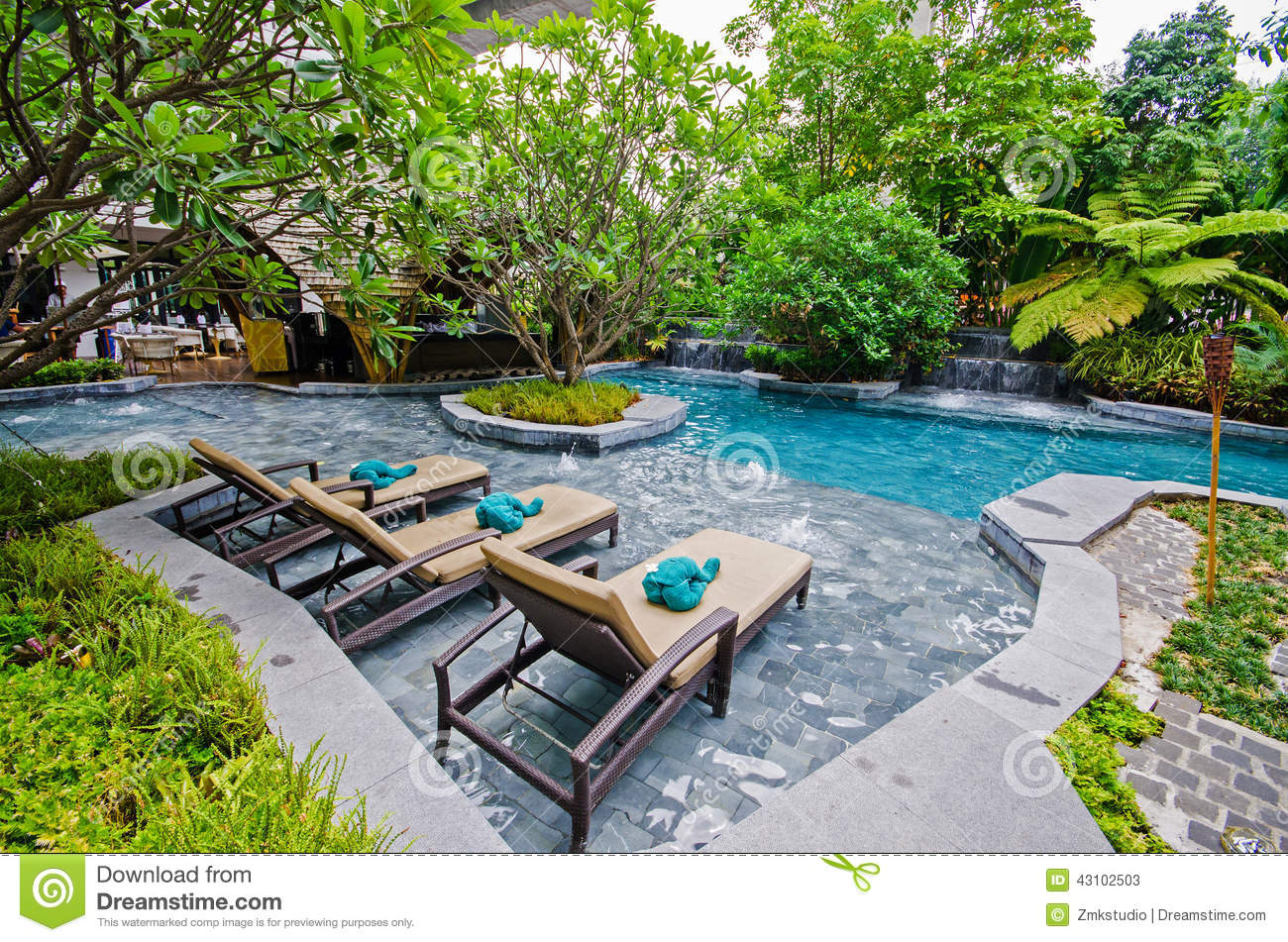 Poolside relax chairs in swimming pool stock image image for Garden swimming pool b q