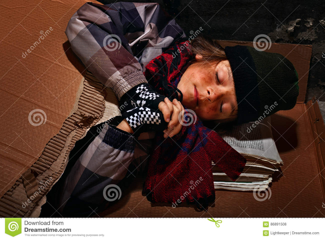Poor beggar boy preparing to sleep on the street - covered with