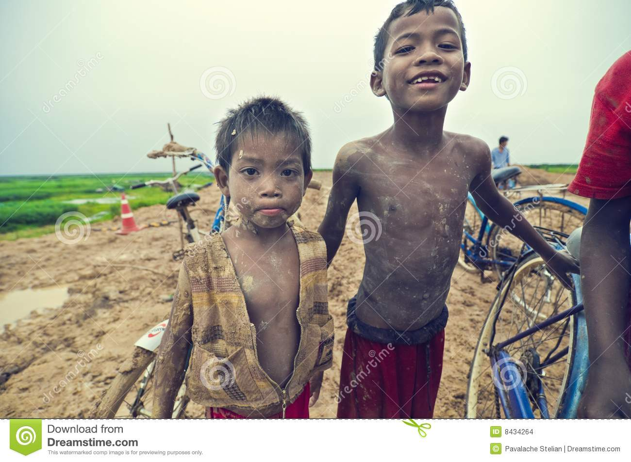 Poor cambodian kids playing with bicycle