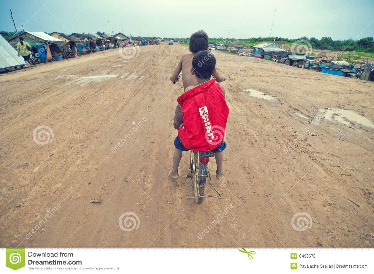 Poor cambodian kids racing with old bicycle