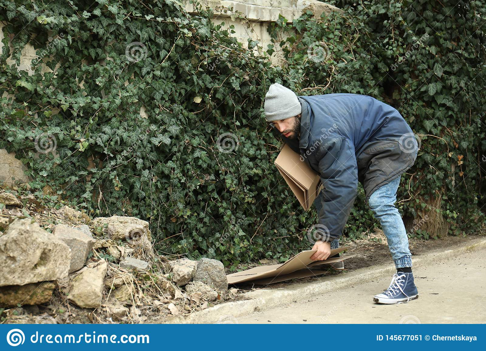Poor homeless man with cardboard