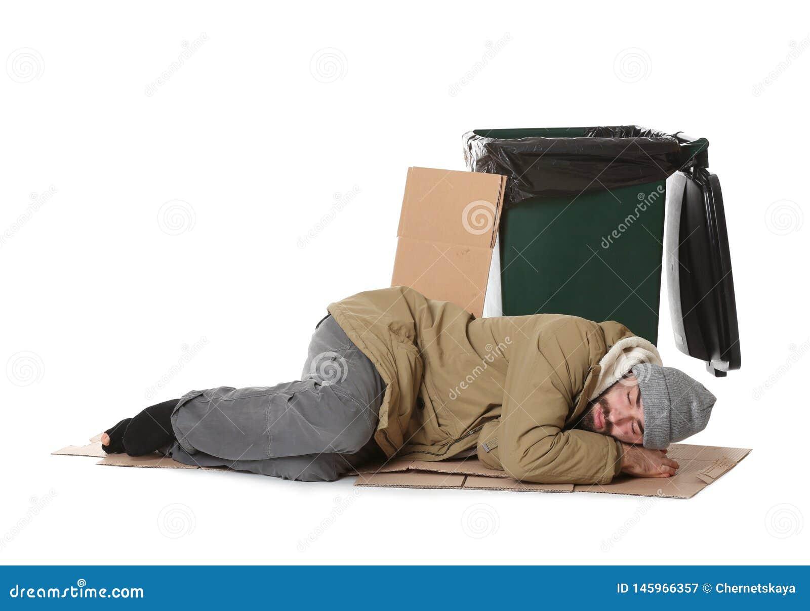 Poor homeless man lying near trash bin