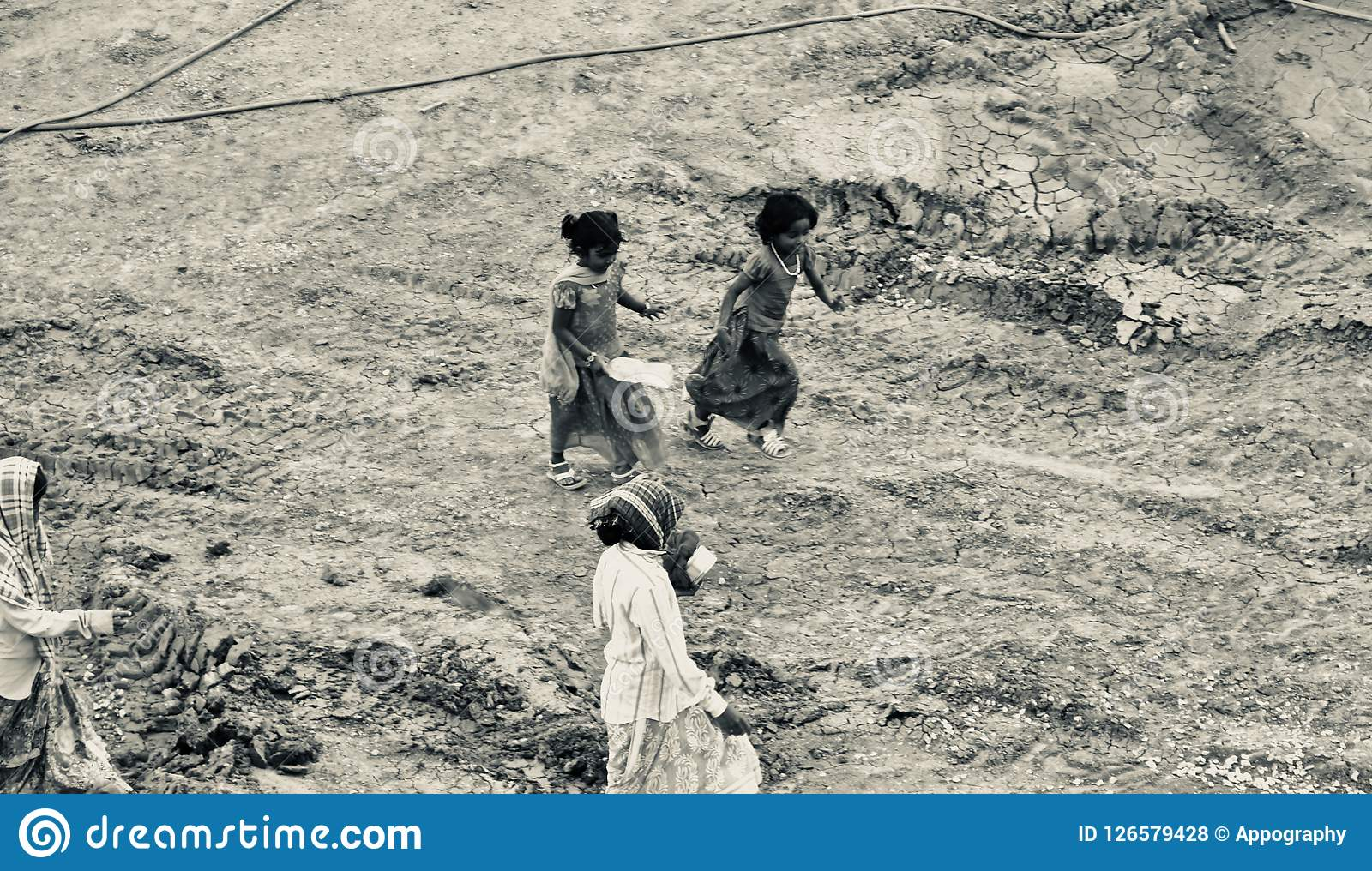 Poor Indian women workers walking through a construction site
