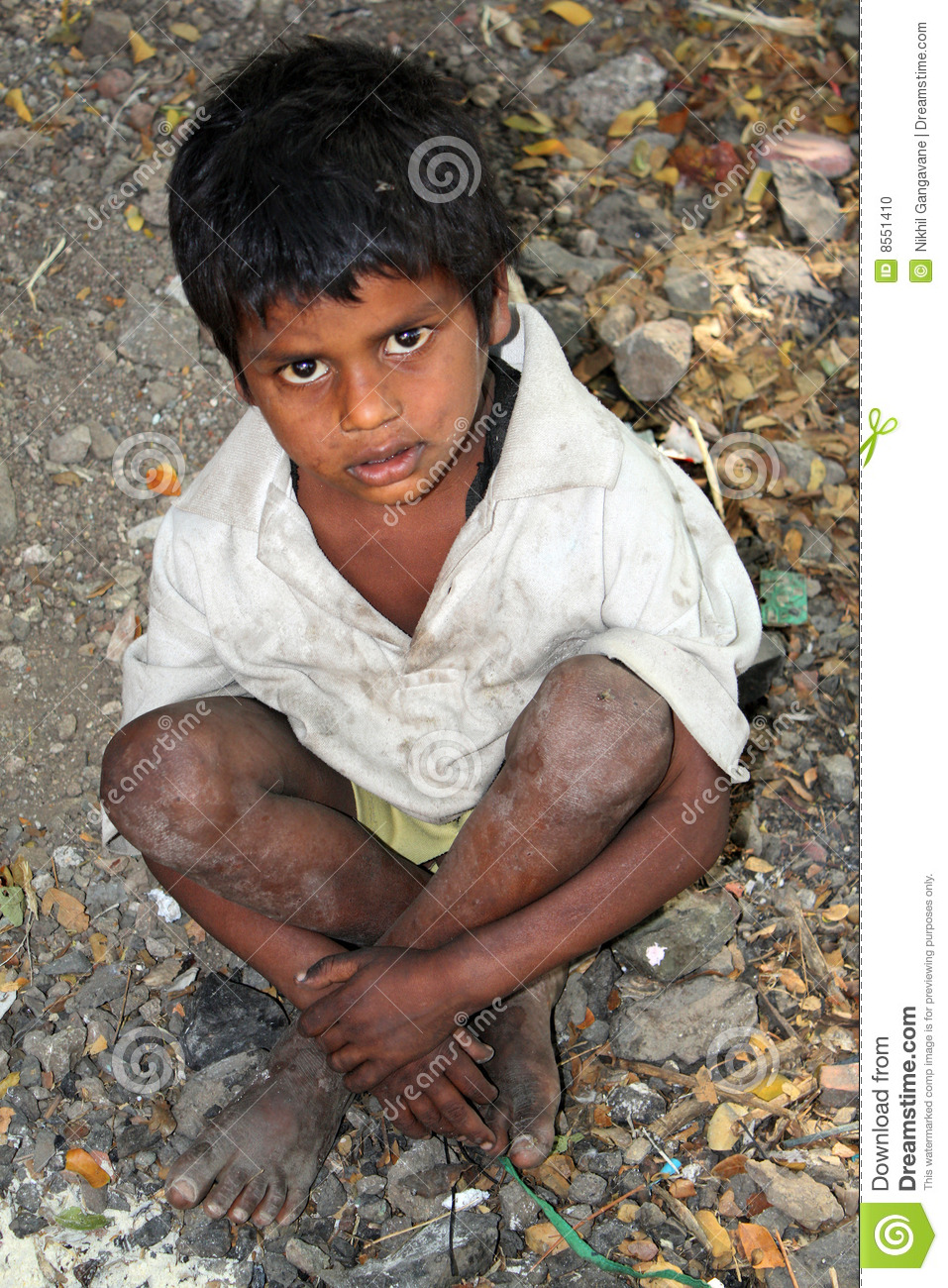 poor kid in India, sitting on the streetside.