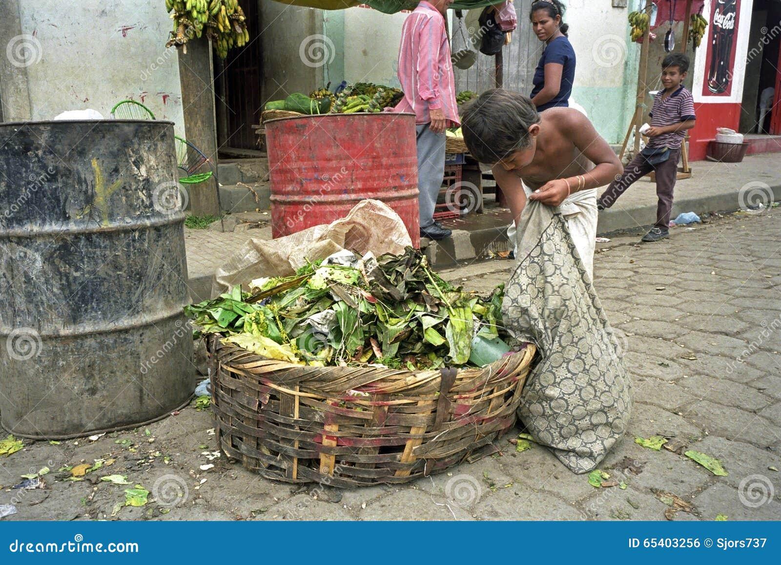 Poor Latino Boy gets food from waste bin, Nicaragua