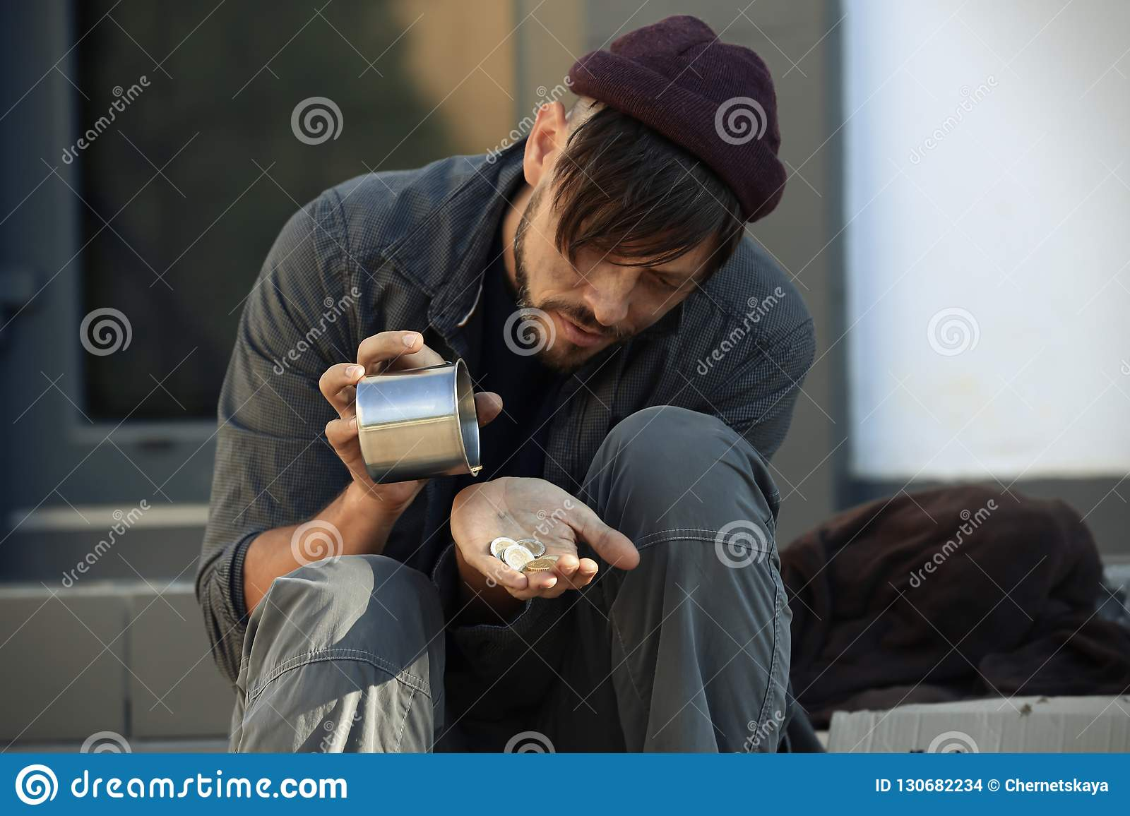Poor man with mug counting coins