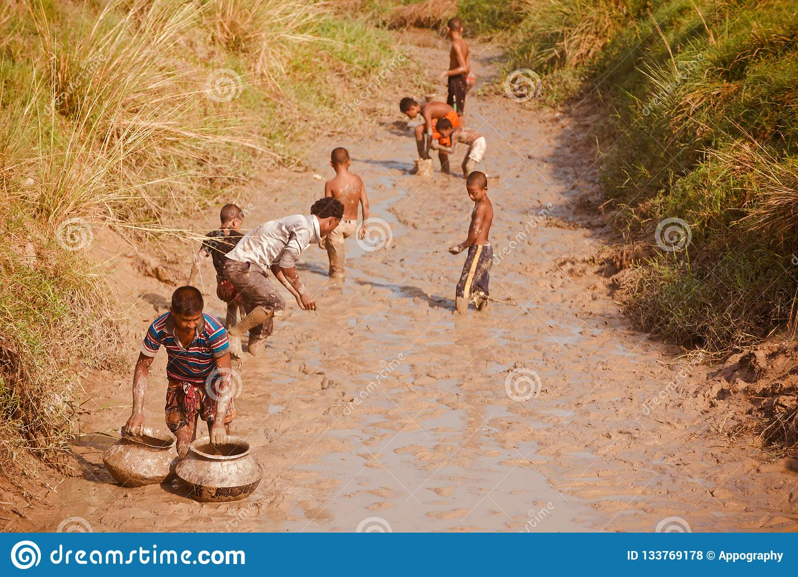 Poor people fishing around a muddy area