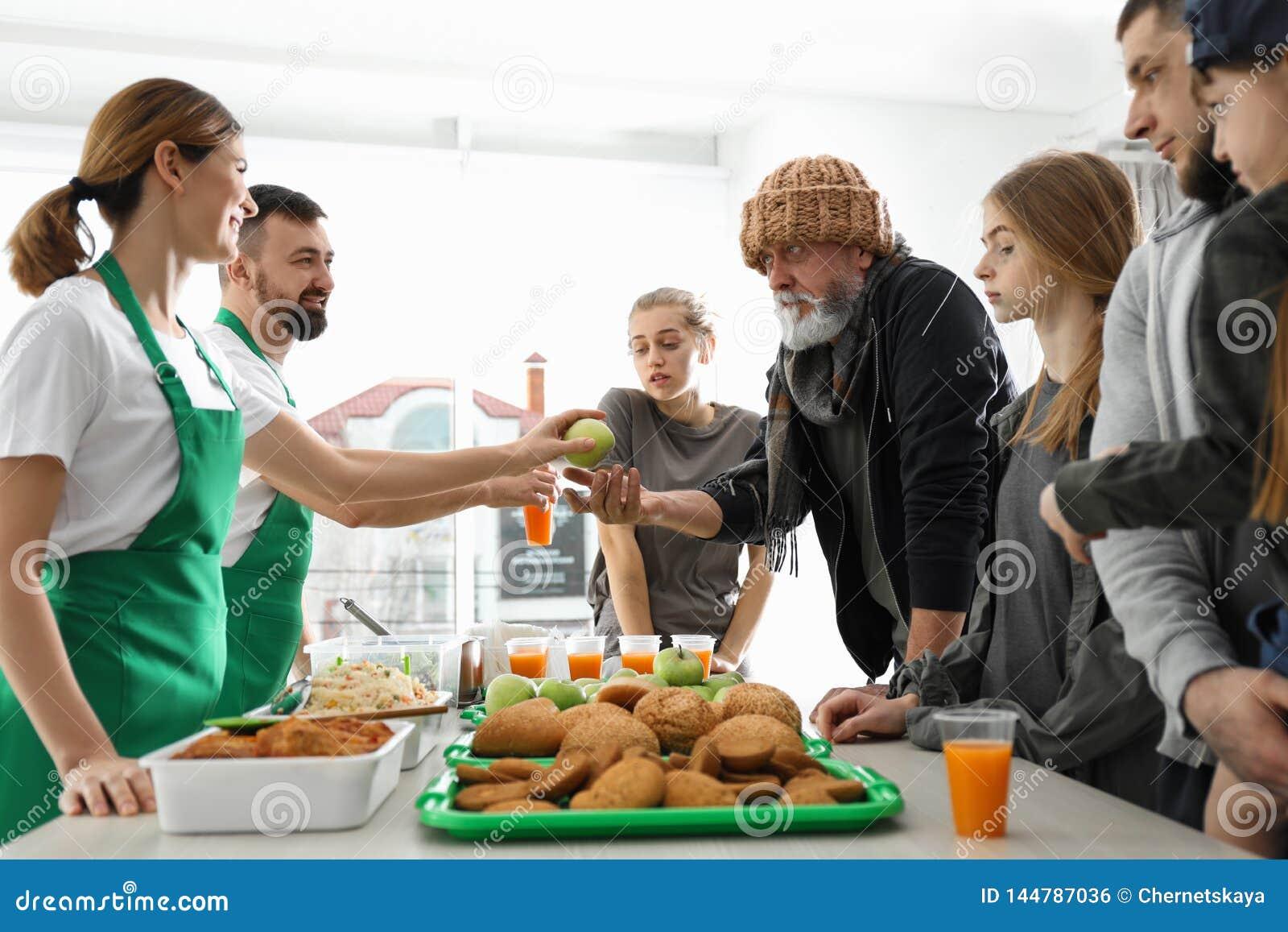 Poor people receiving food from volunteers
