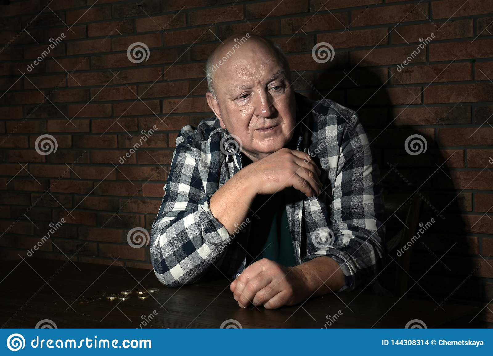 Poor senior man with coins at table near wall
