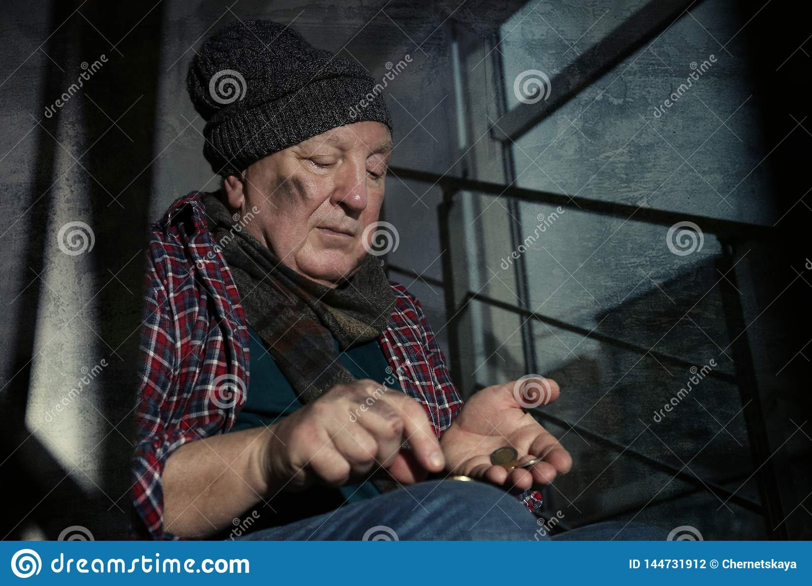 Poor senior man counting coins