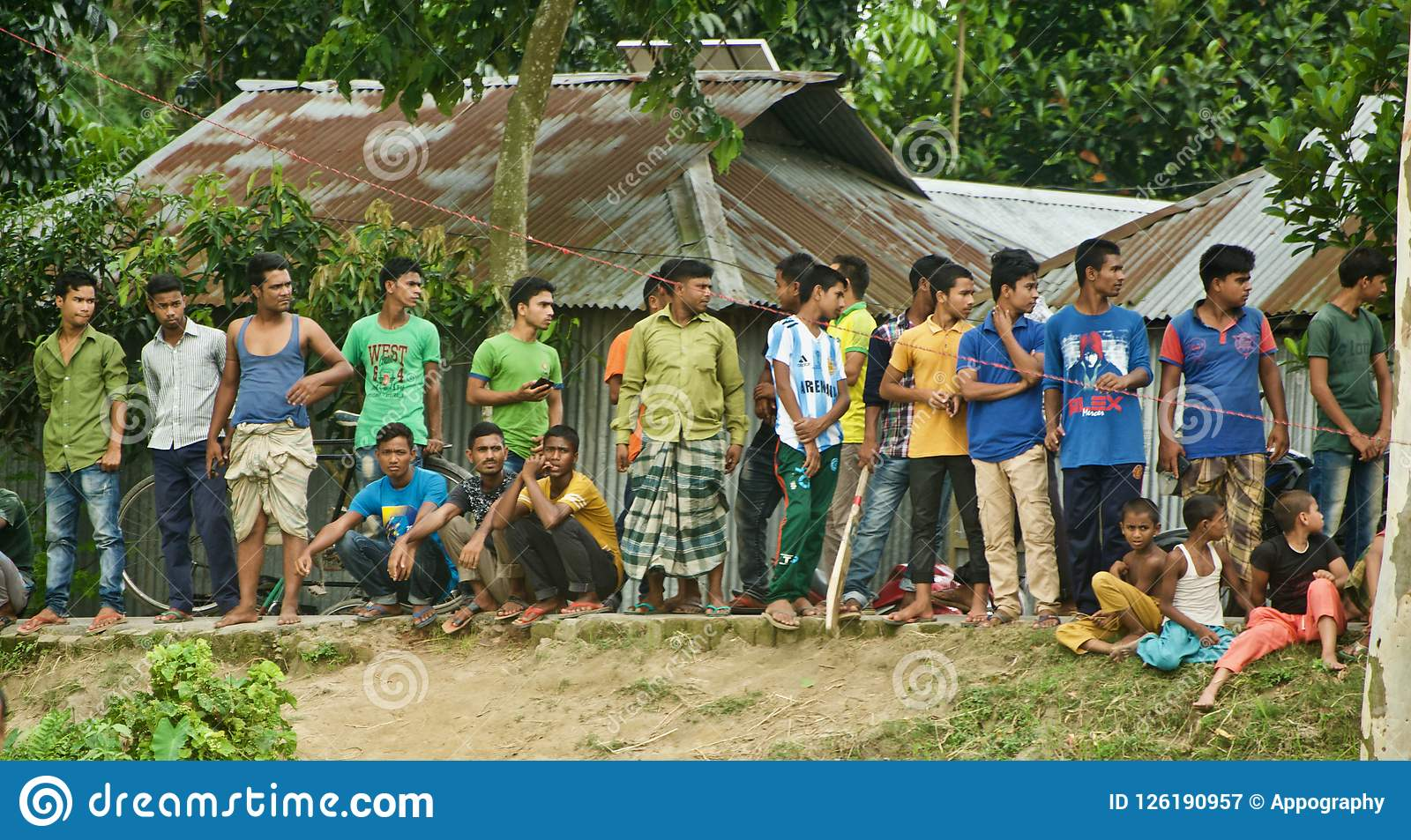 Village people standing on a road to watch a cricket match in Bangladesh