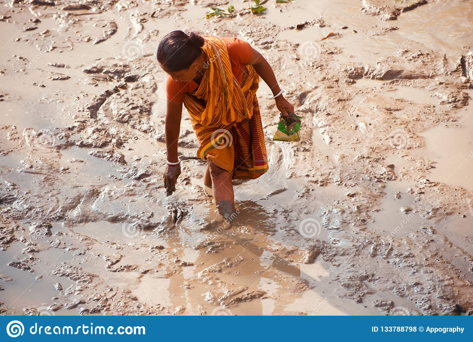 Poor woman fishing around a muddy place