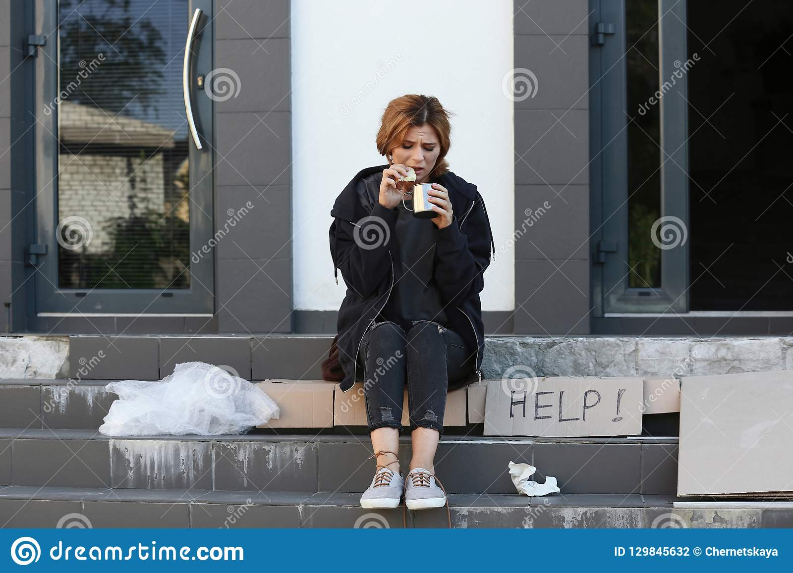 Poor woman with piece of bread and mug