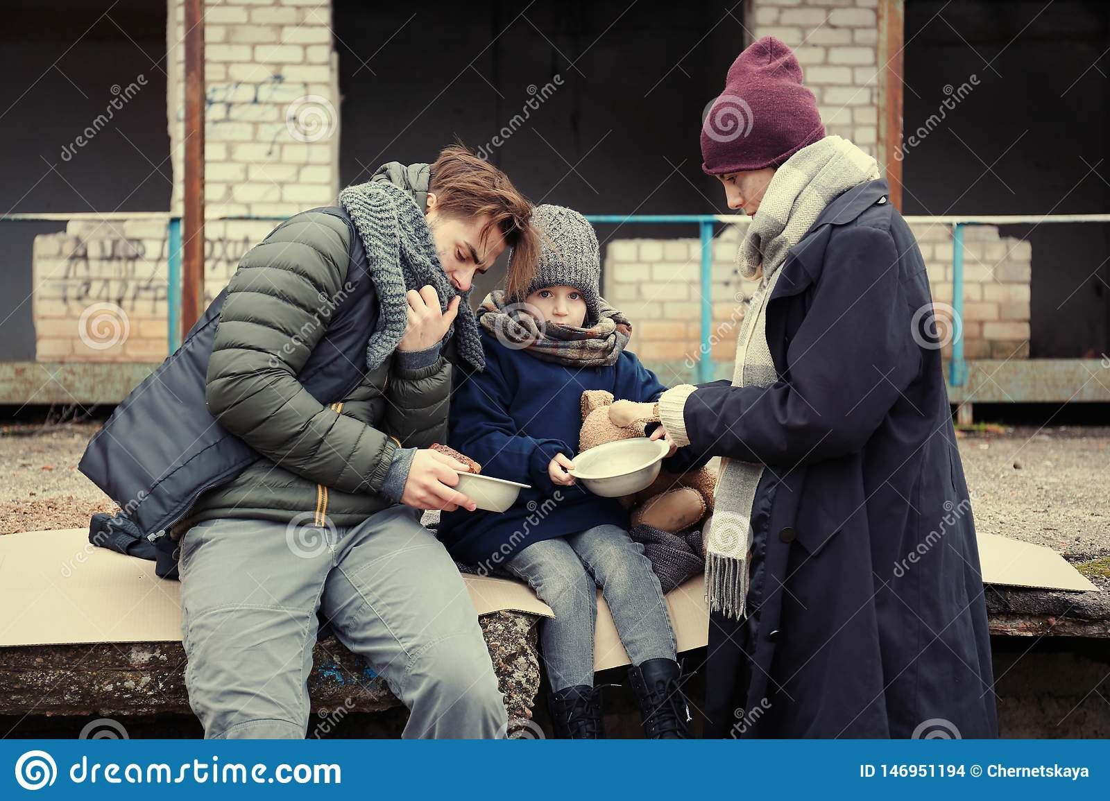 Poor young family with bread on street