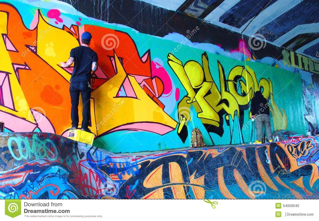 Graffiti artist spray painting wall at skateboard tunnel vancouver b c