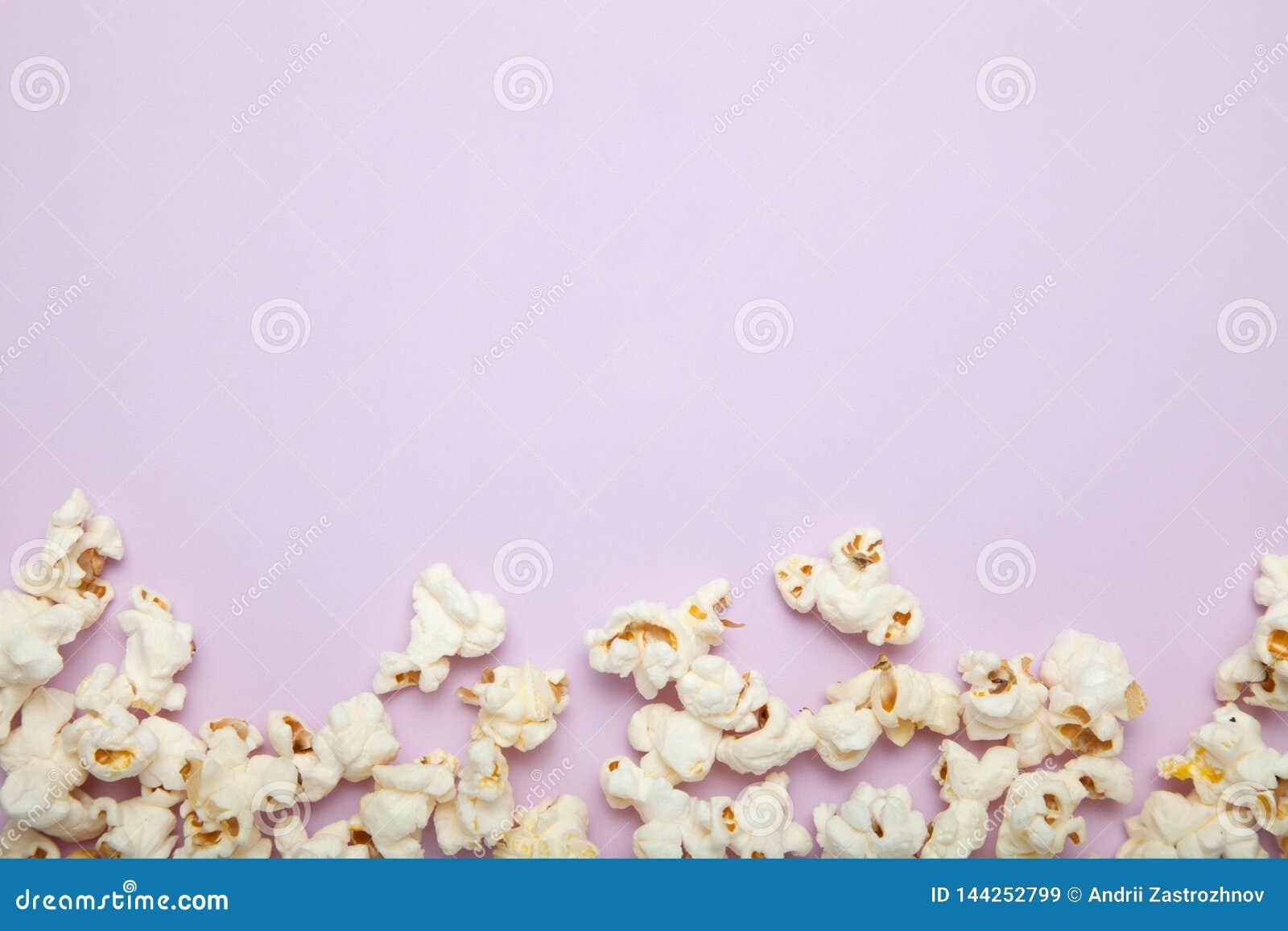 Popcorn σε ένα ρόδινο υπόβαθρο, κενό διάστημα για το κείμενο