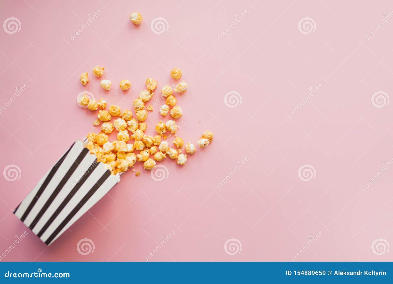 Popcorn in der Papiertüte zerstreut auf Draufsicht des Rosahintergrundes