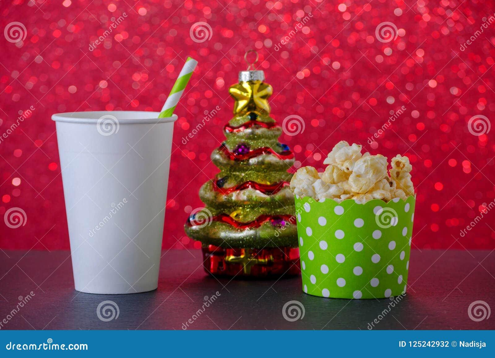Popcorn-, drink- och julträdgarnering för film på röd bokehbakgrund, selektiv fokus