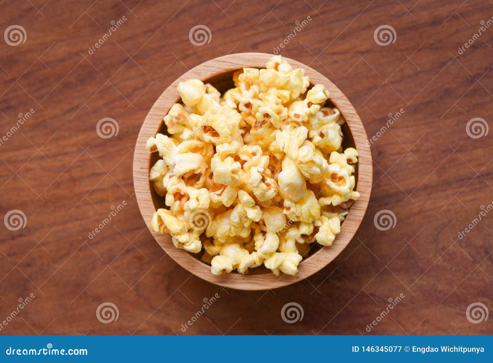 Popcorn i träbästa sikt för koppbunke- och träbackgroubd/sött smörpopcorn saltar