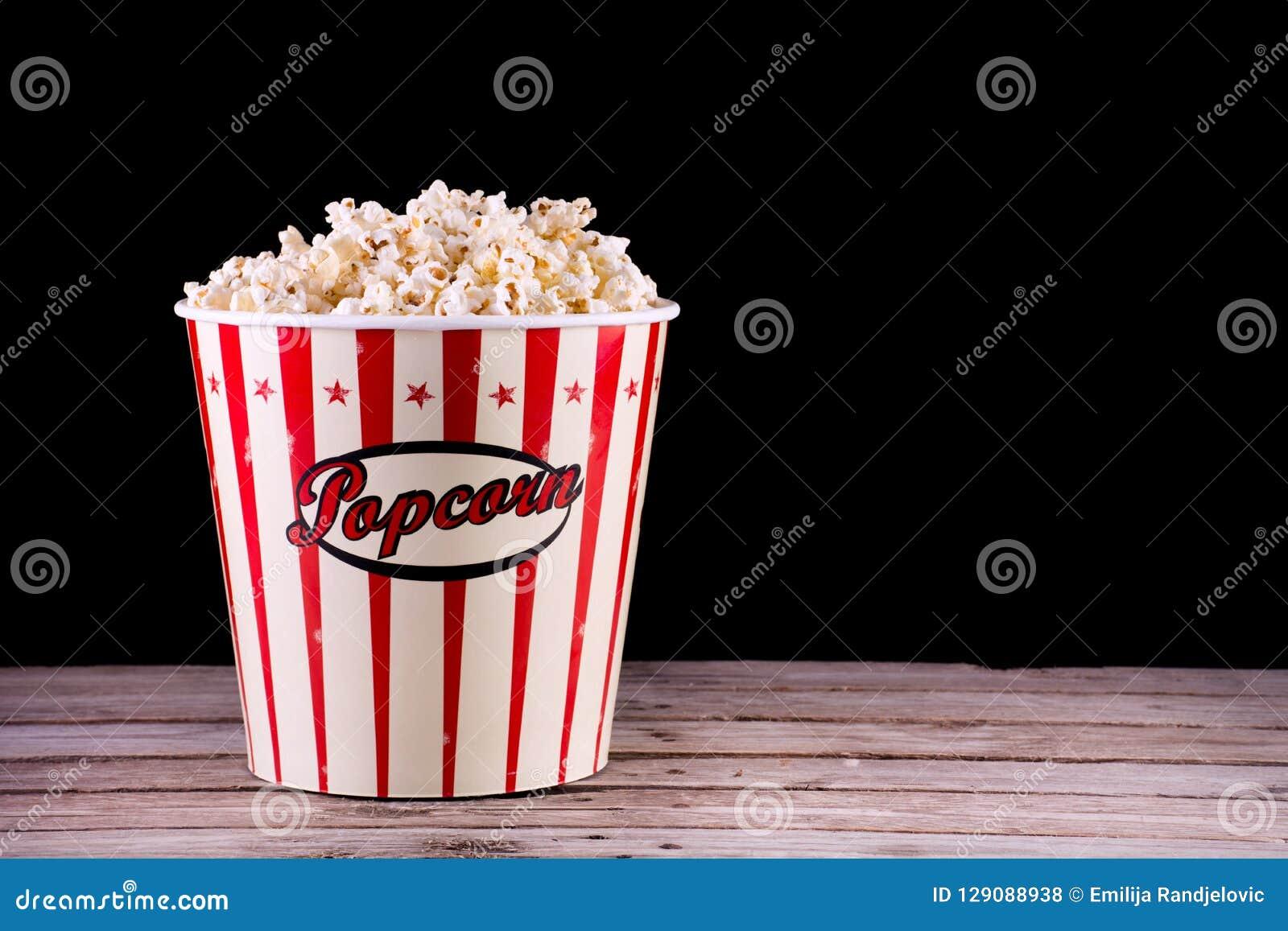 Popcorn im vollen Retro- Kasten auf hölzernem rustikalem Schreibtisch