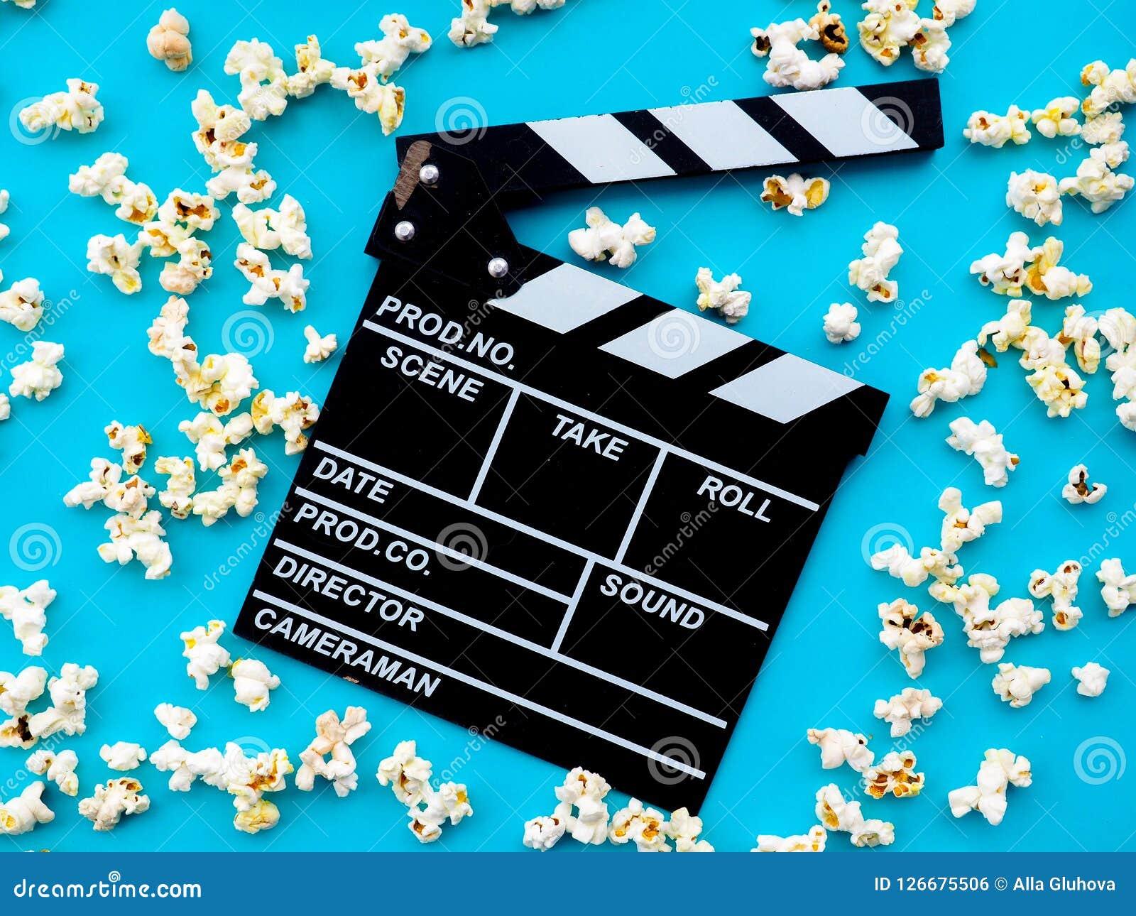 Popcorn och clapperboard på blå bakgrund begreppet av filmen, film, underhållning som annonserar