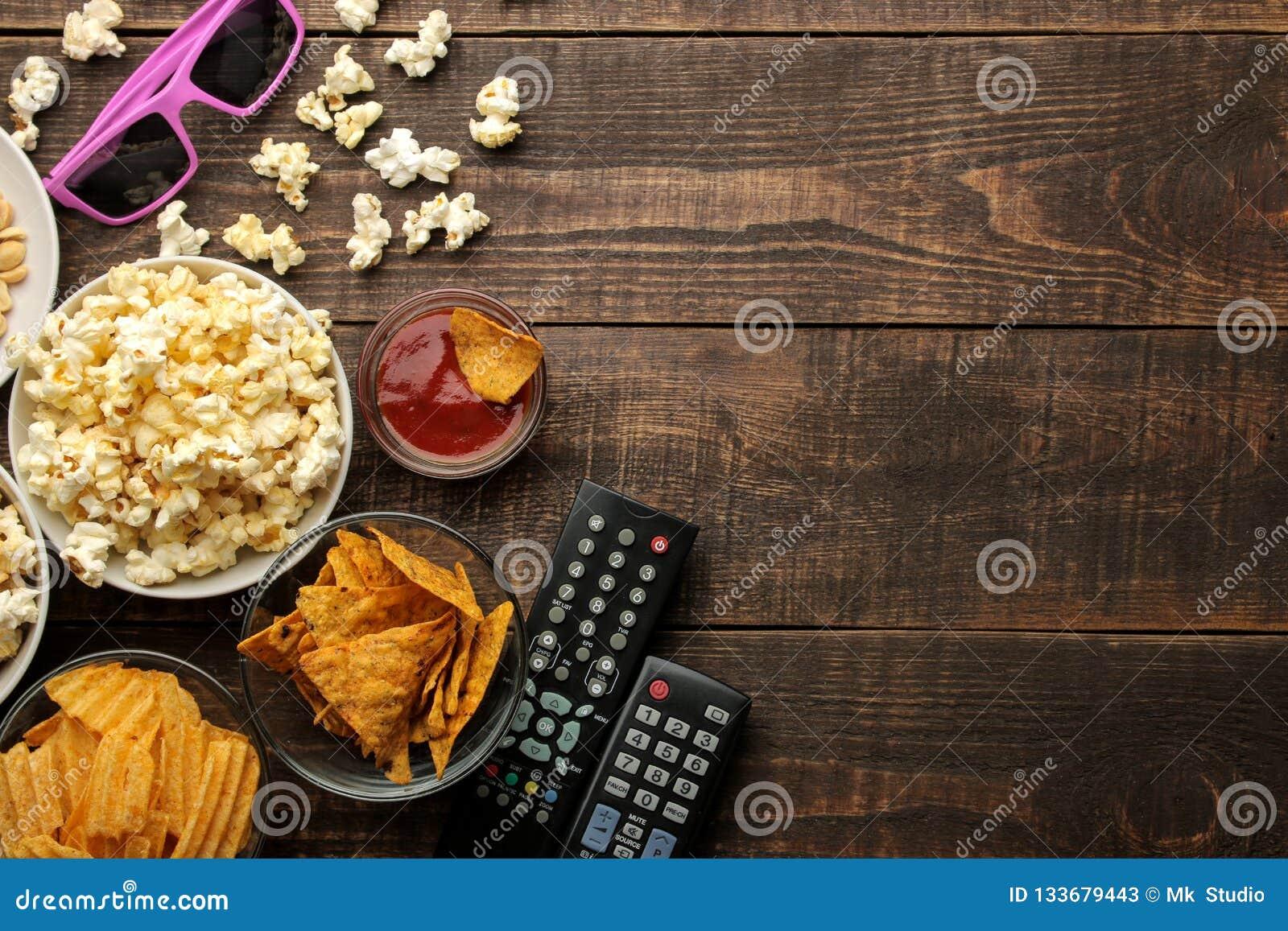 Popcorn och olika mellanmål, 3D exponeringsglas, TVfjärrkontroll på en brun träbakgrund begrepp av hållande ögonen på filmer hemm
