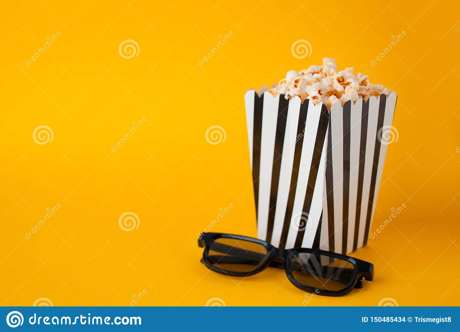 Popcorn in paper bag stand on yellow background top view fnd black 3d glasses