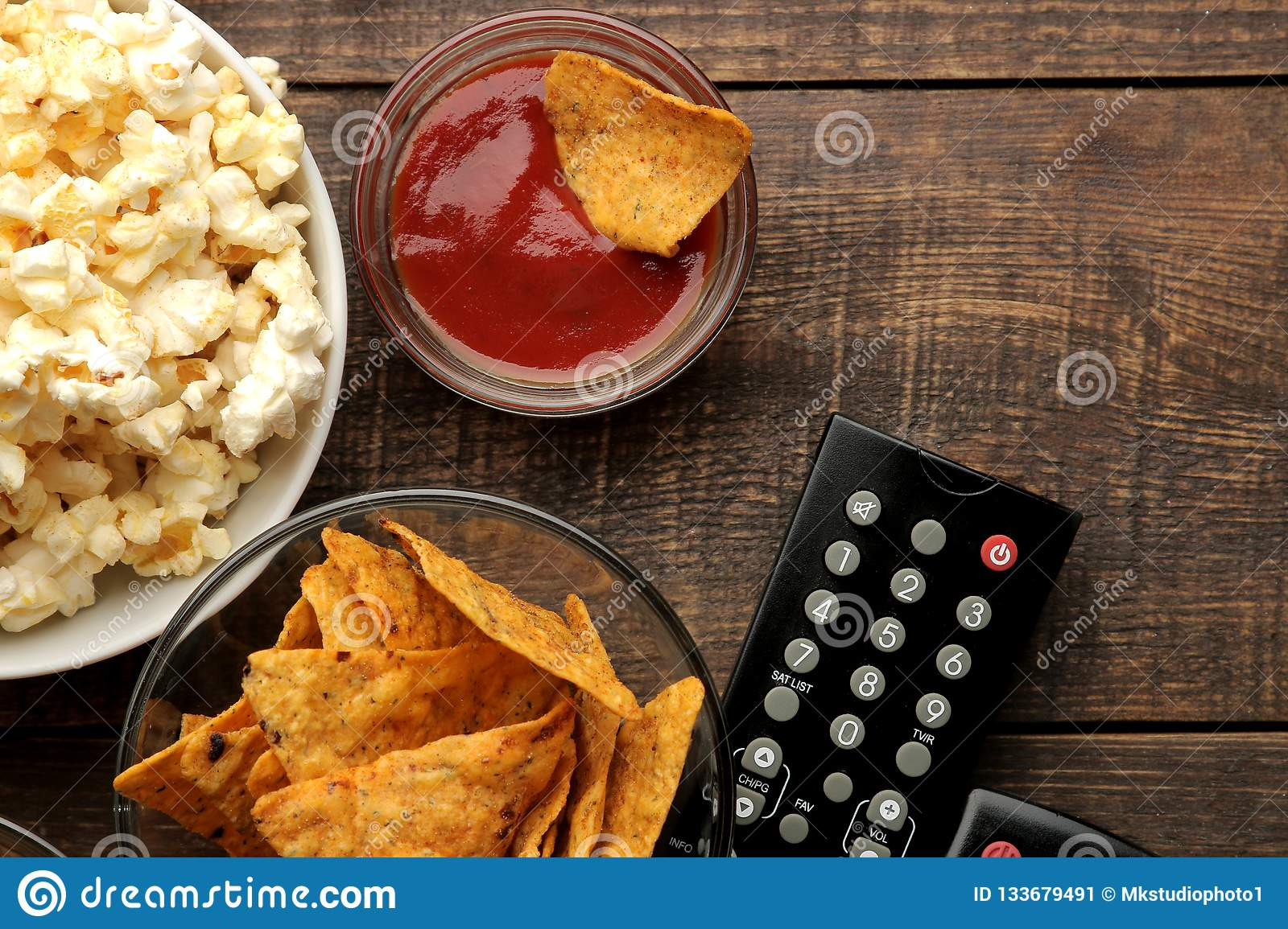 Popcorn and various snacks, TV remote on a brown wooden background. concept of watching movies at home. view from above