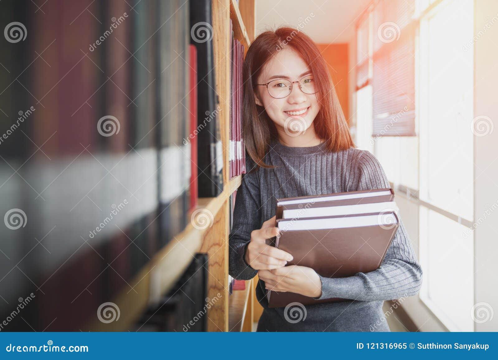 Popiera edukaci szkolnej wiedzy szkoły wyższa uniwersytecki pojęcie, Piękny żeński student collegu trzyma ona książki ono uśmiech