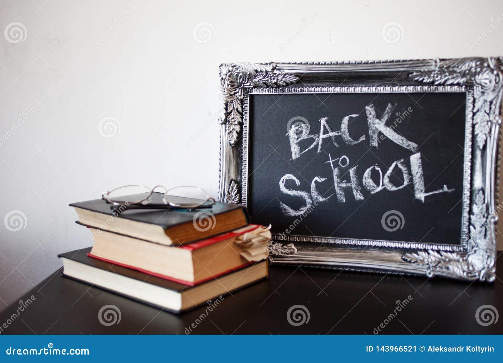 Popiera szkoła, kreda w rocznik ramie Tekst na chalkboard i sterta podręczniki