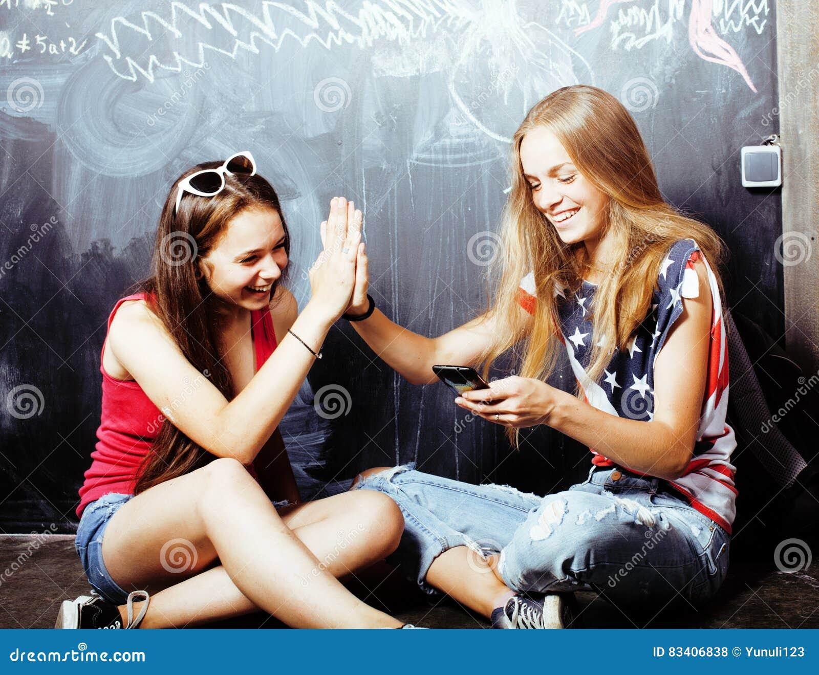 Popiera szkoła po wakacji, dwa nastoletniej istnej dziewczyny w sala lekcyjnej z blackboard malującym wpólnie