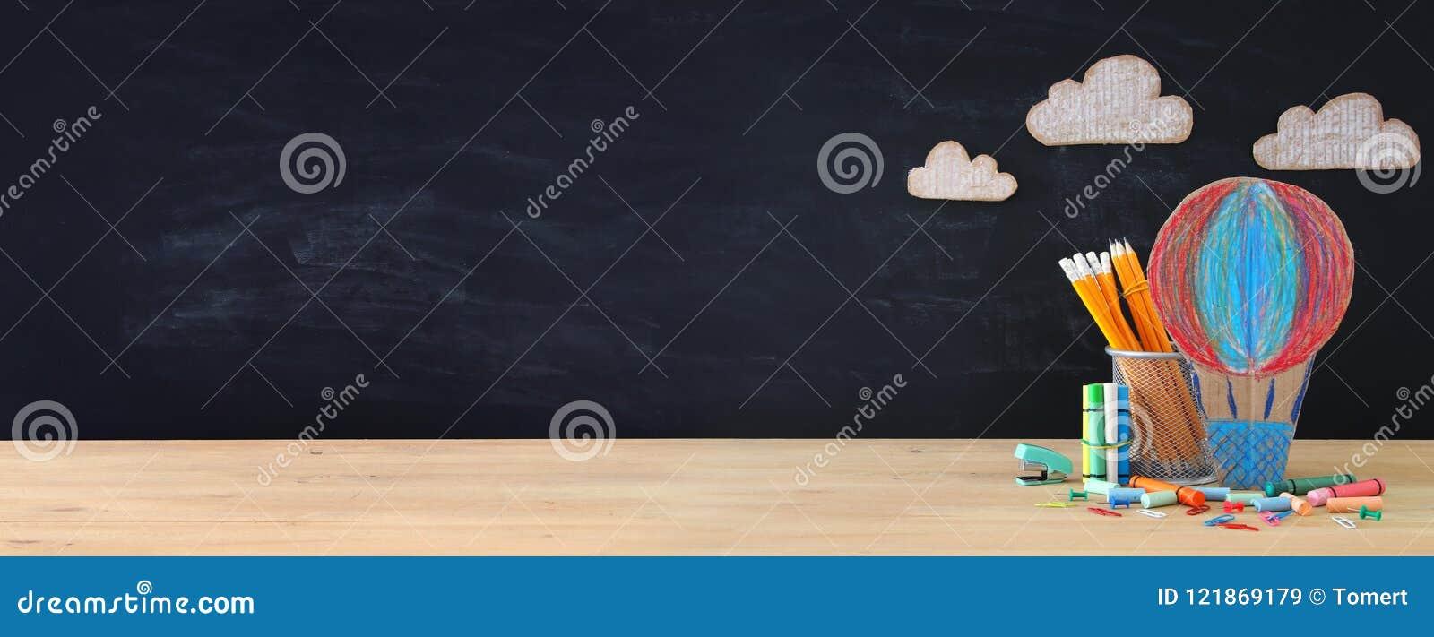 Popiera szkoły pojęcia sztandar gorącego powietrza ballon i ołówki przed sala lekcyjnej blackboard